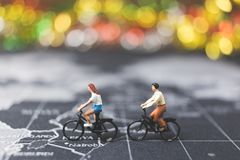 Miniature people travelers riding bicycle on world map. Traveling and exploring the world Concept Stock Photography