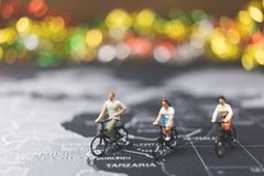 Miniature people travelers riding bicycle on world map. Traveling and exploring the world Concept Stock Photos