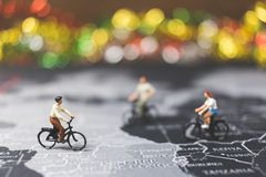 Miniature people travelers riding bicycle on world map Stock Photography
