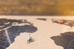 Miniature people travelers riding bicycle on world map , Traveli. Ng and exploring the world Concept Royalty Free Stock Photos