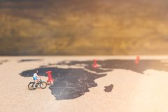 Miniature people travelers riding bicycle on world map , Traveli. Ng and exploring the world Concept Stock Image