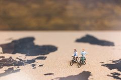 Miniature people travelers riding bicycle on world map , Traveli. Ng and exploring the world Concept Stock Photos