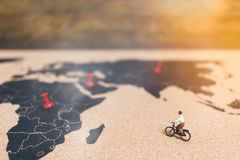 Miniature people travelers riding bicycle on world map , Traveli. Ng and exploring the world Concept Stock Photography