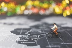 Miniature people travelers riding bicycle on world map. Traveling and exploring the world Concept Stock Photo