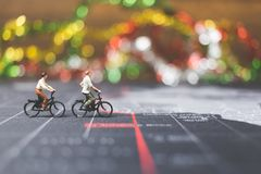 Miniature people travelers riding bicycle on world map. Traveling and exploring the world Concept Stock Images