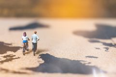 Miniature people travelers riding bicycle on world map , Traveli. Ng and exploring the world Concept Royalty Free Stock Photo