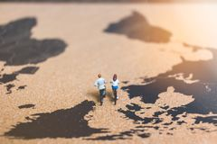 Miniature people travelers riding bicycle on world map , Traveli. Ng and exploring the world Concept Stock Photo