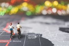 Miniature people travelers riding bicycle on world map. Traveling and exploring the world Concept Royalty Free Stock Image