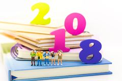 Miniature people, travelers standing on the book in the New Year in 2018, traveling to destination. Used in the travel business concept Royalty Free Stock Image