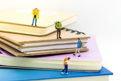 Miniature people, travelers standing on the book, traveling to destination. Used in the travel business concept Stock Photos