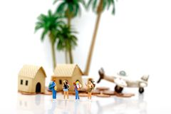 Miniature people: Travelers standing with houses and planes on c royalty free stock image