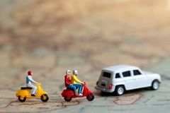 Miniature people: Traveller riding a motorcycle on map with car, Concept of Travel around the world and the adventure. stock photography