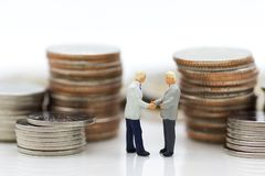 Miniature people : Two businessmen make a deal, with stack of coins to background, using as commitment, agreement, saving, finance. Money, investment and royalty free stock image