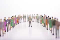 Miniature people in two lines across to each other with boss in. The middle over white background Royalty Free Stock Image