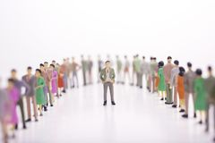 Miniature people in two lines across to each other. Miniature people in two lines across to each other with boss in the middle over white background Stock Images