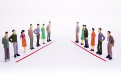 Miniature people in two lines across to each other over white ba. Ckground Royalty Free Stock Image
