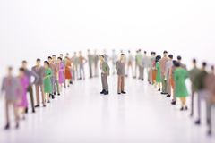 Miniature people in two lines across to each other with two boss. In the middle over white background Royalty Free Stock Photos