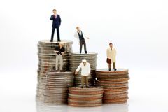 Miniature people with various occupations standing on coins money royalty free stock images