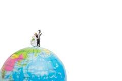 Miniature people wedding , bride and groom couple on The globe Stock Image