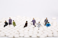 Miniature people with white pill Stock Photo
