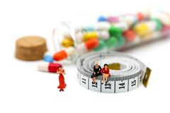 Miniature people : woman sitting on tape Measure with slim body. Woman and drug background Stock Photos