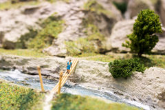 Miniature people: woman walking on the bridge. Macro photo, shallow DOF. Royalty Free Stock Images