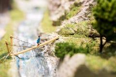 Miniature people: woman walking on the bridge. Macro photo, shallow DOF. Stock Image