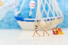 Miniature people : Woman wearing swimsuit is fun together. The ship is background, using as a travel business concept.  Royalty Free Stock Photography