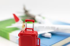 Miniature people: Women standing on red luggage . Image use for travel by plane.  Royalty Free Stock Images