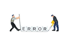 Miniature people. The word error of the cubes. Miniature workers. Human figures. Stock Photos