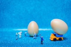 Miniature people work at Easter-eggs for Easter day. On blue glitter background royalty free stock images