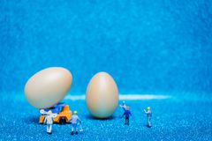 Miniature people work at Easter-eggs for Easter day. On blue glitter background stock images