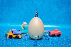 Miniature people work at Easter-eggs for Easter day. On blue glitter background stock photos