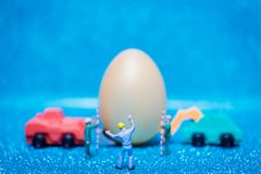 Miniature people work at Easter-eggs for Easter day. On blue glitter background stock photo