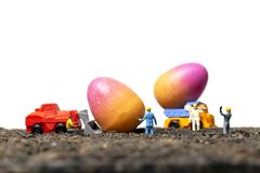 Miniature people work at Easter-eggs for Easter day. With white background stock photo