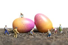 Miniature people work at Easter-eggs for Easter day. With white background stock photography