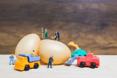 Miniature people work at Easter-eggs for Easter day. On wooden background stock image