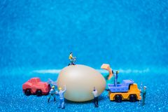 Miniature people work at Easter-eggs for Easter day. On blue glitter background royalty free stock image