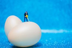 Miniature people work at Easter-eggs for Easter day. On blue glitter background stock image