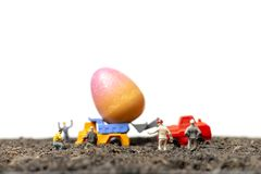 Miniature people work at Easter-eggs for Easter day. With white background royalty free stock images
