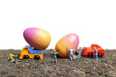 Miniature people work at Easter-eggs for Easter day. With white background royalty free stock image