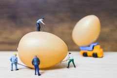 Miniature people work at Easter-eggs for Easter day. On wooden background royalty free stock photos