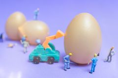Miniature people work at Easter-eggs for Easter day. On violet background royalty free stock image