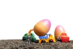 Miniature people work at Easter-eggs for Easter day. With white background royalty free stock photography