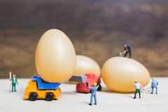 Miniature people work at Easter-eggs for Easter day. On wooden background stock photos
