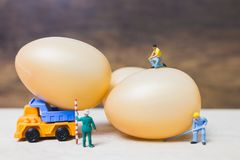 Miniature people work at Easter-eggs for Easter day. On wooden background stock photography
