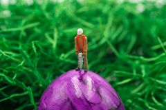 Miniature people work at Easter-eggs. On green background royalty free stock photography