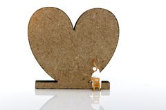 Miniature people: Worker brush painting Wooden Heart. Art of bus stock image