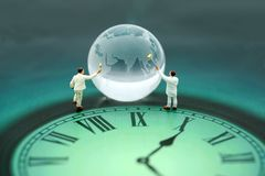Miniature people : worker clean global world with the time,World. Time concept Stock Image