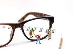 Miniature people worker cleaning eyes glasses on book. Clear Vision concept. stock image